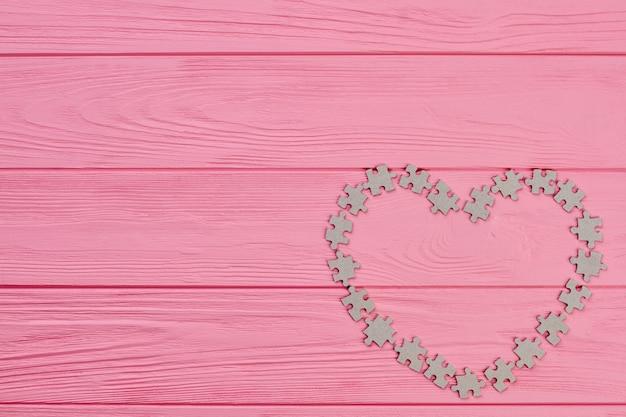Holzhintergrund des valentinstags. herzform aus puzzleteilen und platz für text. urlaub der liebe. valentinstag grußkarte.