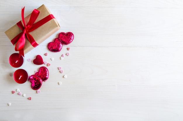 Holzhintergrund des valentinstags mit rotem herzen, geschenken und kerzen. geschenke zum valentinstag. weißer hölzerner hintergrund