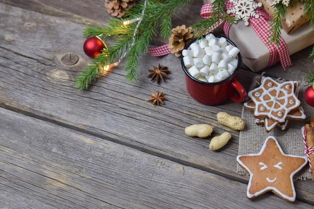 Holzhintergrund mit einem weihnachtszweig von kaffee und keksen mit platz für text.