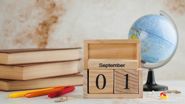 Holzkalender 1. september auf einem stapel bücher, globus. wissenstag, beginn des schuljahres. speicherplatz kopieren.