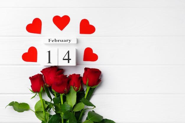 Holzkalender 14. februar und rosen auf weißem hintergrund flach liegen