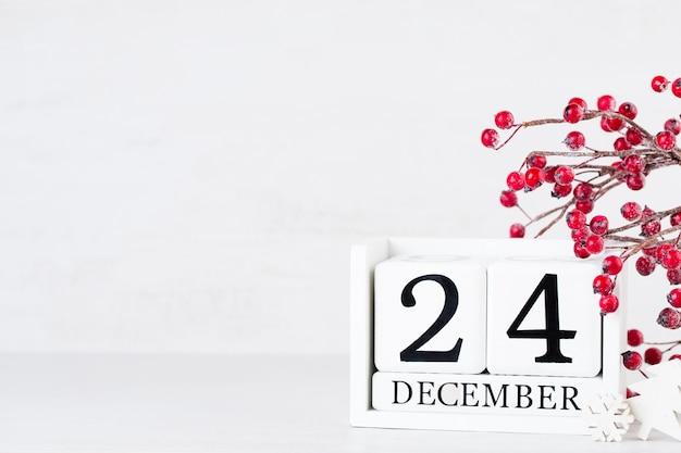 Holzkalender 24. dezember weihnachtskonzept tag. auf einem grauen hintergrund mit weihnachtsdekor.