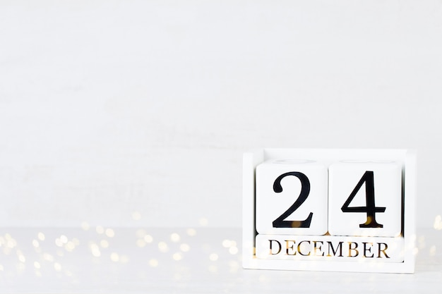 Holzkalender 24. dezember weihnachtstag. auf einem grau mit weihnachtsdekor.