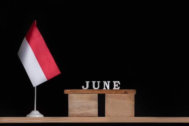 Holzkalender juni mit polnischer flagge auf schwarzer oberfläche. feiertage von polen im juni.