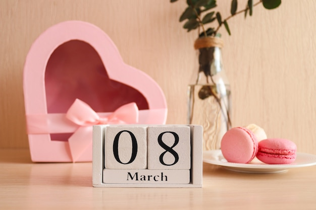 Holzkalender märz, ein glas champagner, französisches makronengebäck und eine herzförmige geschenkbox