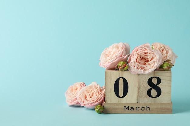 Holzkalender mit 8 märz und rosen auf blauem hintergrund