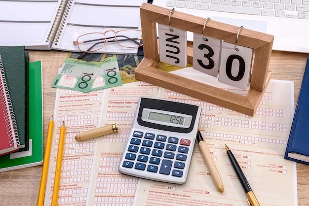 Holzkalender mit australischer steuererklärung auf dem tisch
