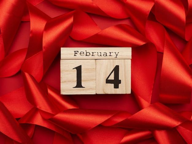 Holzkalender mit datum 14. februar auf rotem seidenband, valentinstag