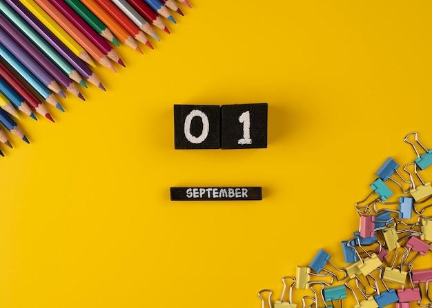 Holzkalender mit dem datum 1. september auf gelbem hintergrund mit büroklammern und bleistiften