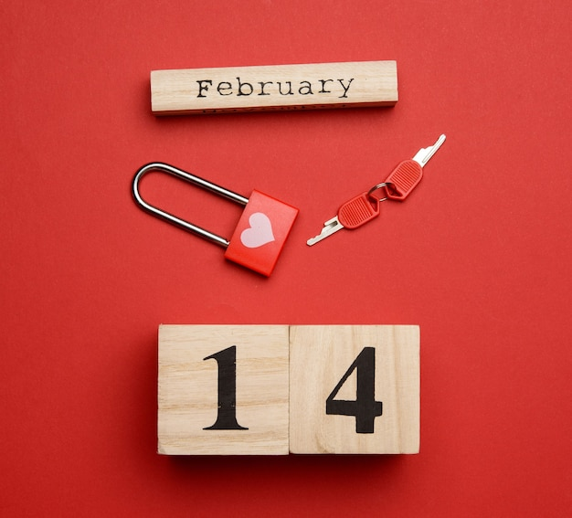 Holzkalender mit dem datum des 14. februar und einem schloss mit einem schlüssel auf einem roten hintergrund, draufsicht