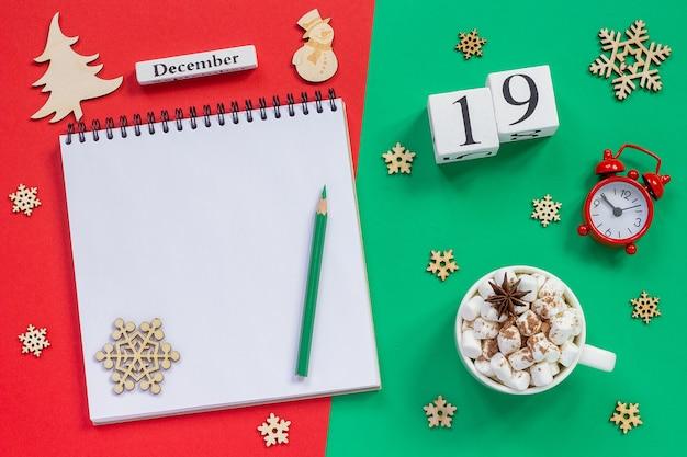 Holzkalender mit notizbuch und tasse heißem kakao