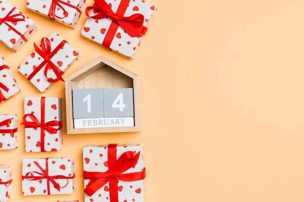 Holzkalender, umgeben von verpackten geschenkboxen mit bändern und textilen herzen