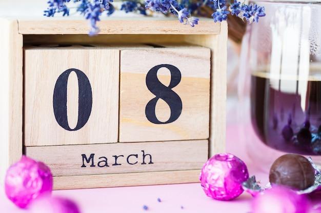 Holzkalender und eine tasse kaffee mit süßigkeiten auf dem tisch. feier des internationalen frauentages am 8. märz