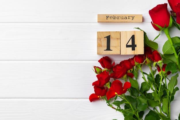 Holzkalender und rosen auf weißer oberfläche
