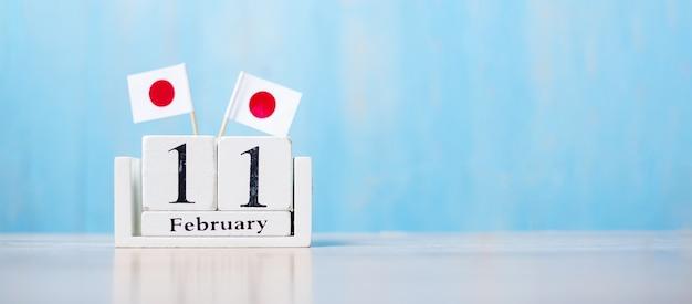 Holzkalender vom 11. februar mit miniatur-japan-flaggen.