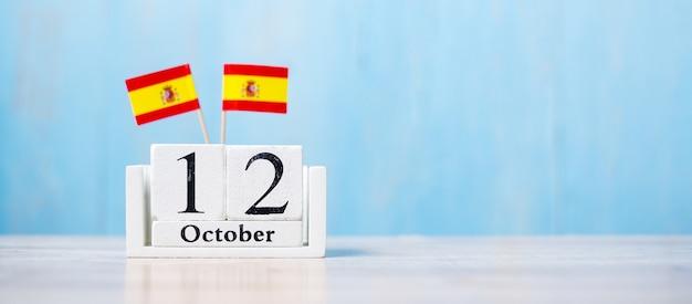Holzkalender vom 12. oktober mit miniatur-spanien-flaggen.
