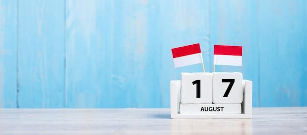 Holzkalender vom 17. august mit miniatur-indonesien-flaggen. indonesiens unabhängigkeitstag, nation holiday day und fröhliche feierkonzepte