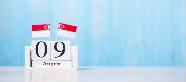 Holzkalender vom 9. august mit miniaturflaggen von singapur. singapurs unabhängigkeitstag, stadtstaat-nationalfeiertag und fröhliche feier-republik-konzepte