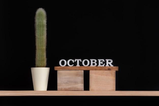 Holzkalender von oktober und kaktus auf schwarzem hintergrund. attrappe, lehrmodell, simulation.