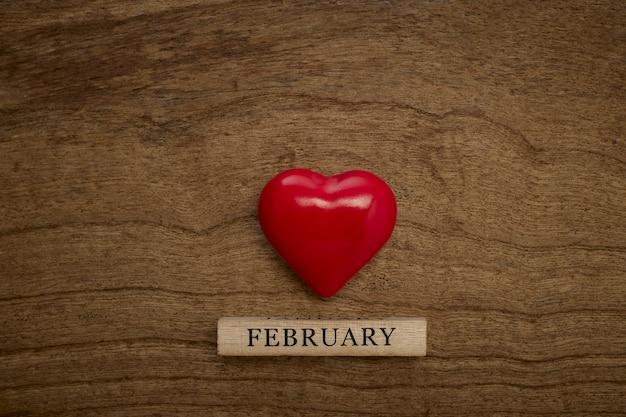 Holzkalendershow vom 14. februar mit einem roten herzen auf hölzerner beschaffenheit, draufsicht