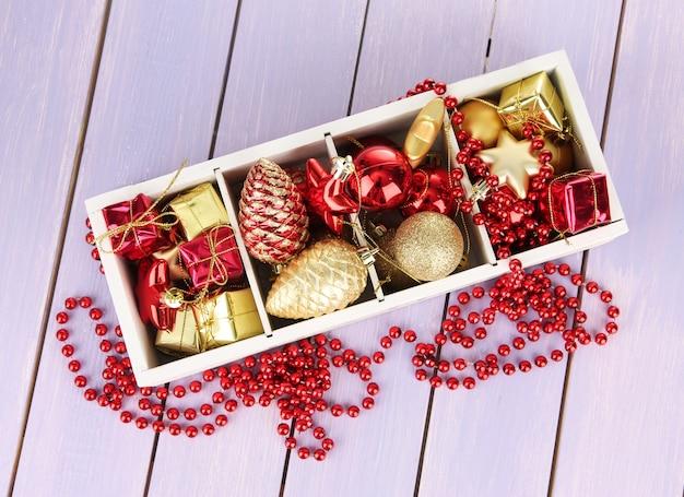 Holzkiste gefüllt mit weihnachtsschmuck, auf farbigem holztisch