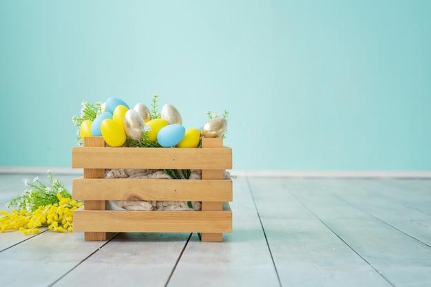 Holzkiste mit blauen, gelben und goldenen ostereiern gegen eine blaue wand