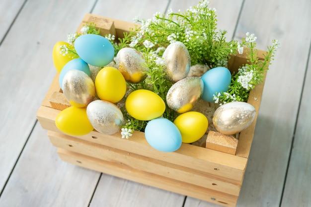 Holzkiste mit blauen, gelben und goldenen ostereiern
