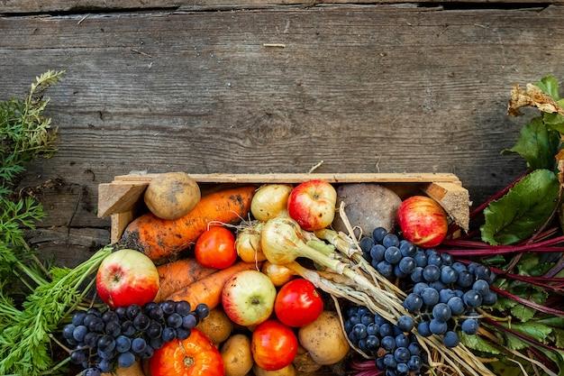 Holzkiste mit draufsicht des frischgemüses und der früchte, nahaufnahme, organisches gemüse. das konzept eines gartens, häuschens, ernte.