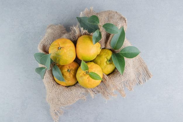 Holzkiste mit einem stück stoff bedeckt, gefüllt mit mandarinen auf marmor.