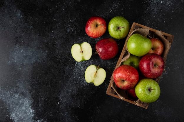 Holzkiste mit frischen bio-äpfeln auf schwarzer oberfläche. .