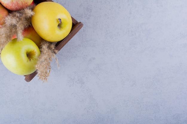 Holzkiste mit frischen grünen äpfeln auf stein.