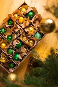 Holzkiste mit goldenen und grünen kugeln und spielzeug für die dekoration, weihnachten und neujahr