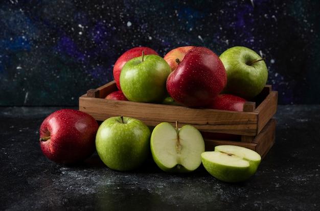 Holzkiste mit reifen bio-äpfeln auf schwarzer oberfläche. .