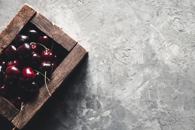 Holzkiste mit süßer kirsche auf blauem hintergrund. platz für text. kirschen in einer holzkiste. konkreter hintergrund