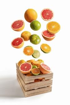 Holzkiste mit verschiedenen fliegenden orangen und mandarinen, isoliert vom weißen hintergrund
