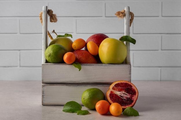 Holzkiste mit verschiedenen frischen tropischen früchten auf dem tisch. bio-ernte