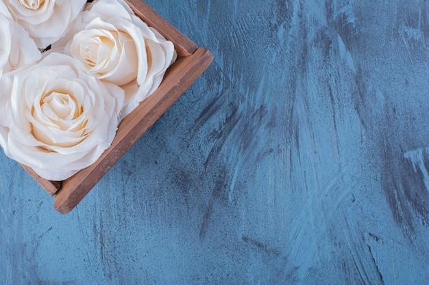 Holzkiste mit weißen rosenblüten auf blau.