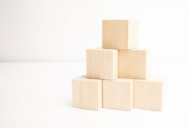Holzklötze, die als pyramidentreppe auf weißem hintergrund stapeln.