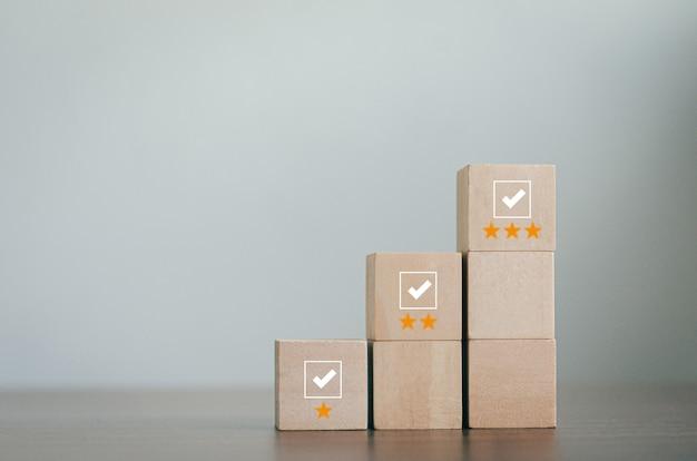 Holzklötze im prüfkonzept erhebungs- und bewertungskonzept die holzklötze sind in einer pyramide angeordnet. würfel mit häkchen-symbol auf holzblock grauer hintergrund mit textfreiraum
