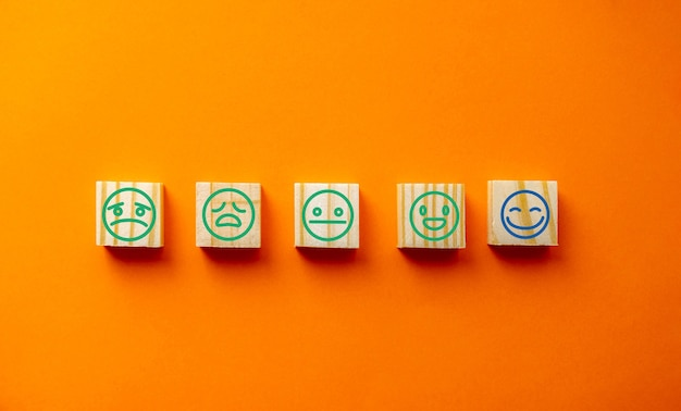 Holzklötze mit dem freudigen gesicht grinsen gesicht zeichen symbol auf blauem hintergrund, bewertung, bewertung erhöhen, kundenerfahrung, zufriedenheit und erstklassiges service-bewertungskonzept
