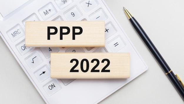 Holzklötze mit dem text ppp 2022 liegen auf hellem hintergrund auf einem weißen taschenrechner. in der nähe ist ein schwarzer griff. geschäftskonzept