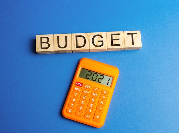 Holzklötze mit dem wort budget und taschenrechner 2021. geld ansammeln und budget planen.
