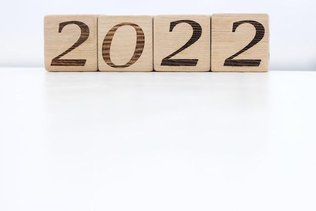 Holzklötze mit den nummern 2022 auf weißer fläche im freien