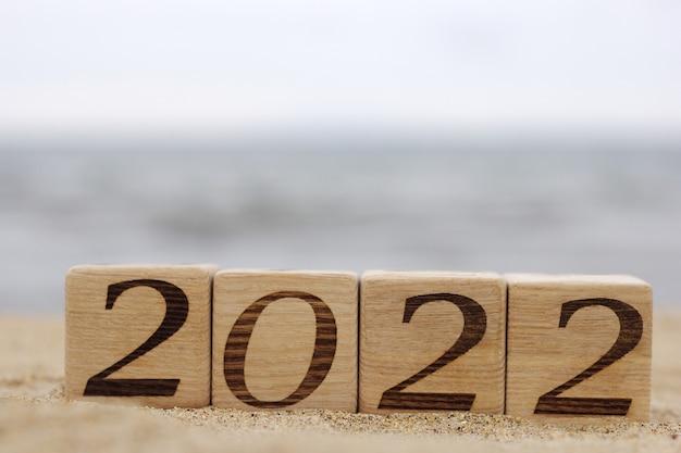 Holzklötze mit den nummern 2022 befinden sich im sand am strand in der nähe des meeres