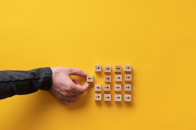 Holzklötze mit einem pfeil, der in die entgegengesetzte richtung zeigt wie die gruppe der anderen.