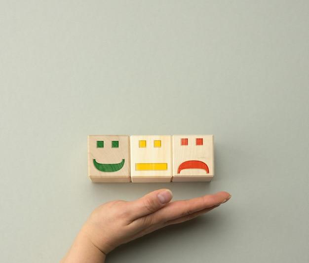 Holzklötze mit unterschiedlichen emotionen von lächeln über traurigkeit bis hin zur hand einer frau. konzept zur bewertung der qualität eines produkts oder einer dienstleistung, des emotionalen zustands und der nutzerbewertungen