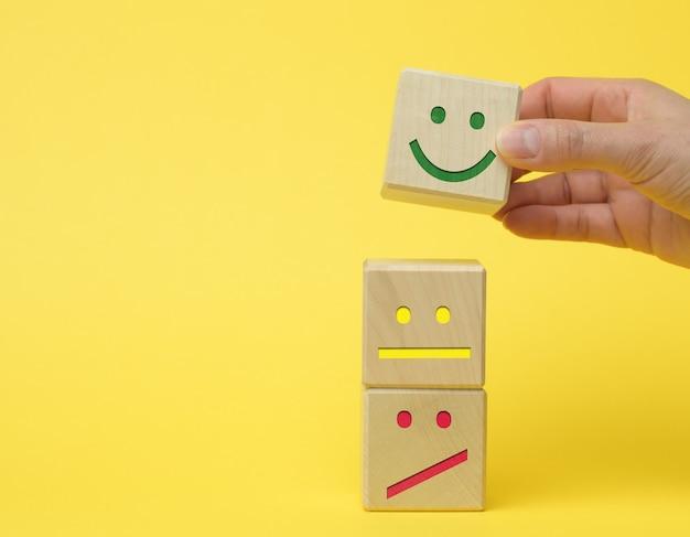 Holzklötze mit unterschiedlichen emotionen von lächeln über traurigkeit bis hin zur hand einer frau