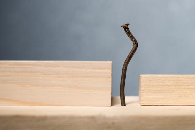 Holzklötze und gebogener nagel. büroangestellter-slouching-konzept.
