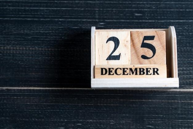 Holzklotzkalender stellte am weihnachtsdatum 25. dezember auf schwarzem hölzernem hintergrund ein.