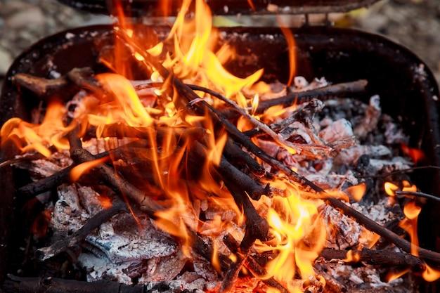 Holzkohle brennt im grill oder im rahmenhintergrund und -beschaffenheit.